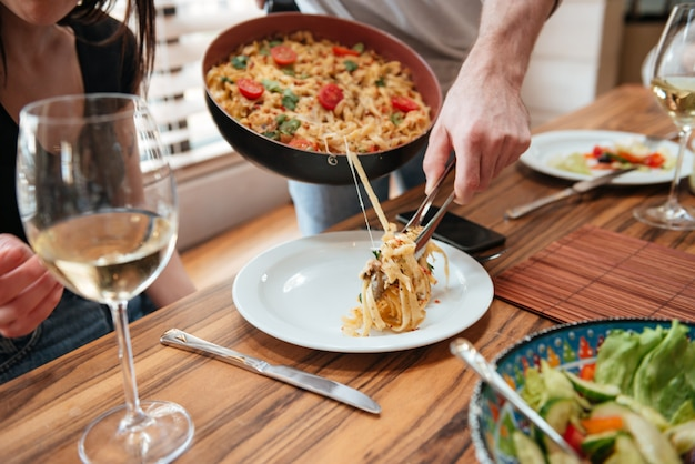 Мужчина готовит обед и кладет еду в тарелку