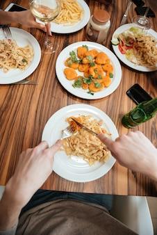 Вид сверху людей, сидящих за столом и едящих макароны