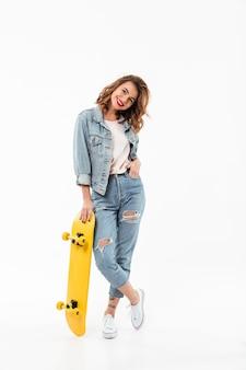 白い壁の上のスケートボードでポーズデニムの服で完全な長さのうれしそうな女性
