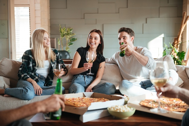 Друзья с пиццей, вином и пивом разговаривают и веселятся