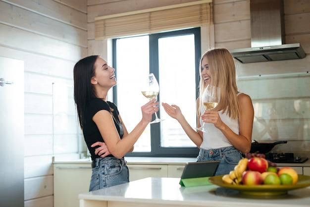 Вид сбоку двух смеющихся женщин, пьющих вино