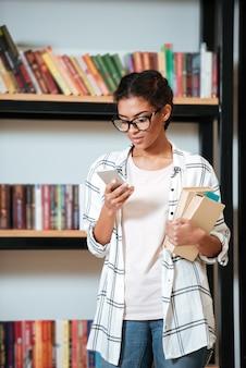 Счастливая африканская дама стоя в библиотеке используя телефон.