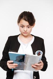 雑誌を保持している混乱している若い女の子