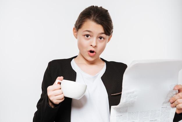読書新聞でコーヒーを飲みながら混乱している若い女の子