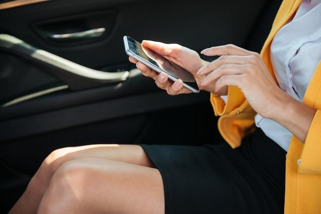 Молодая коммерсантка держа мобильный телефон