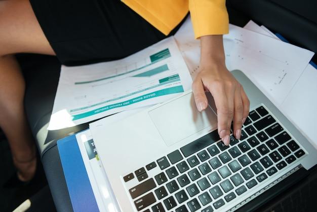 Обрезанное изображение женских рук, работающих с ноутбуком