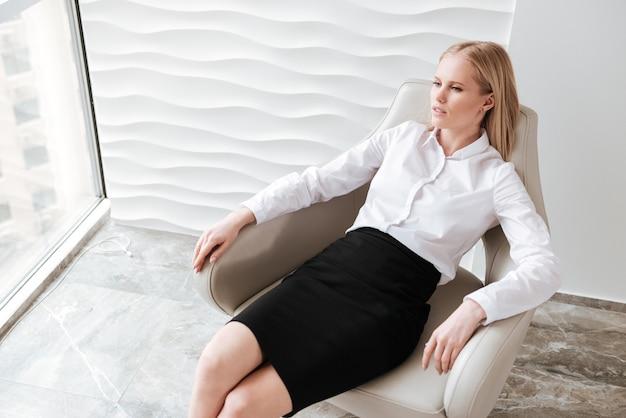 Серьезная коммерсантка сидя в офисе на стуле.