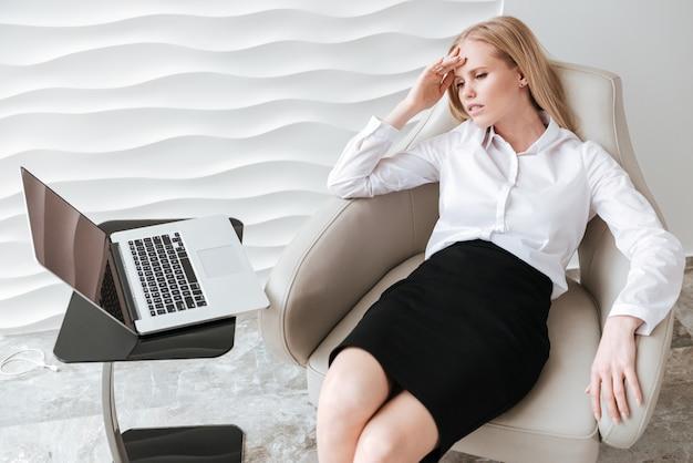 Утомленная коммерсантка сидя в офисе на стуле.
