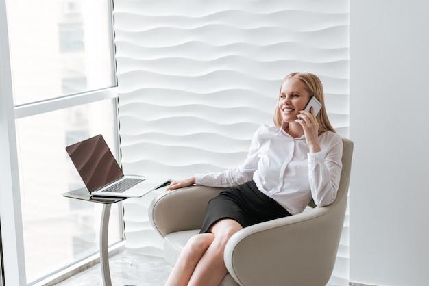 Бизнес-леди, сидя в офисе на стуле. разговор по телефону.