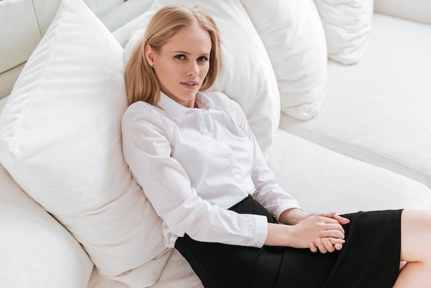 Привлекательный бизнес-леди, сидя в офисе на диване.