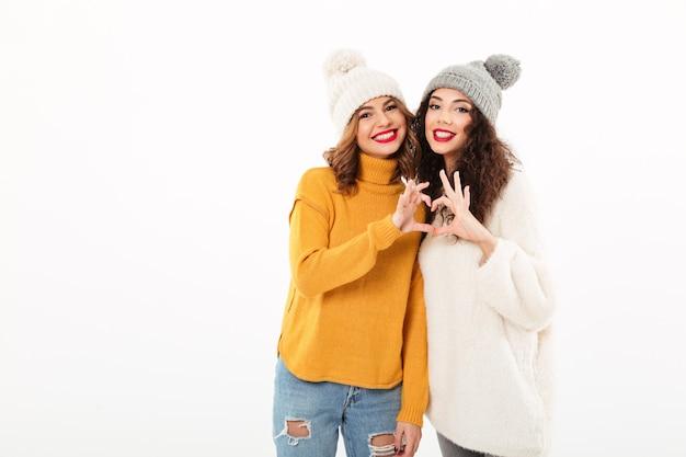 Две улыбающиеся девушки в свитерах и шляпах, делающие знак сердца на белой стене