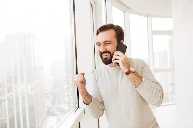ひげと口ひげの携帯電話でビジネスダイアログを成功させながら大きな窓から見ている愛想の良い男