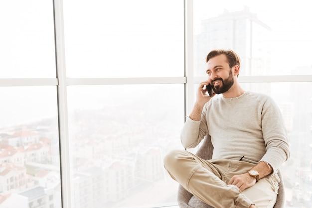 モダンな椅子に座ってフラットで快適なモバイル会話をしながらひげと口ひげの大きな窓から見ている社交的な男