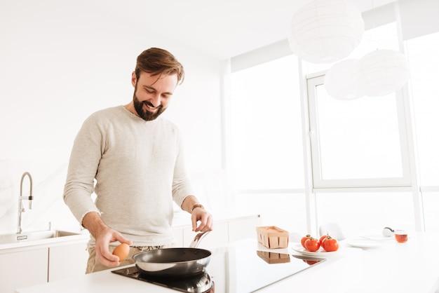 フライパンを使用して、家庭の台所で野菜と短い茶色の髪とひげのオムレツを調理するハンサムな学士の写真