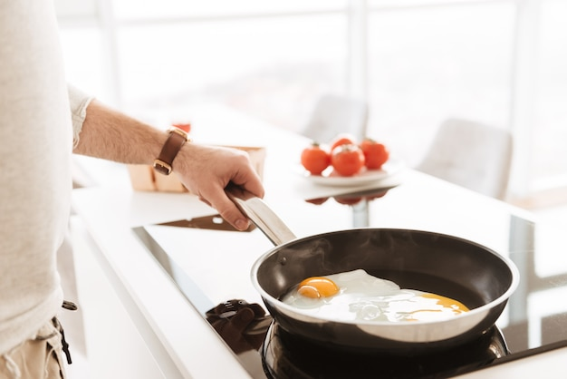 フライパンを使用して家庭の台所で野菜とオムレツを調理する白いシャツの白人の学士号の写真をトリミング
