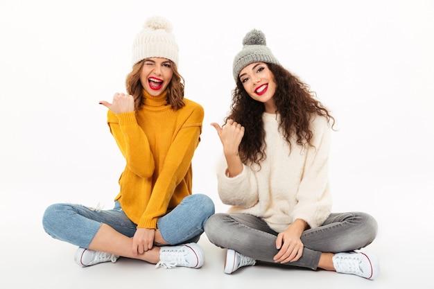 Две игривые девушки в свитерах и шляпах сидят вместе на полу, указывая на белую стену