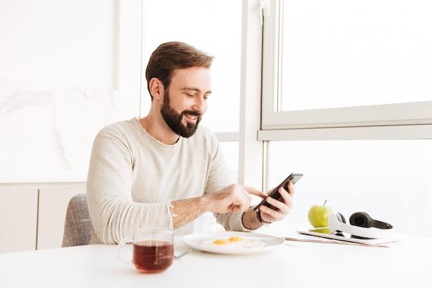 Портрет положительного небритого мужчины в повседневной рубашке, здорового питания с жаркой яиц в квартире, используя смартфон