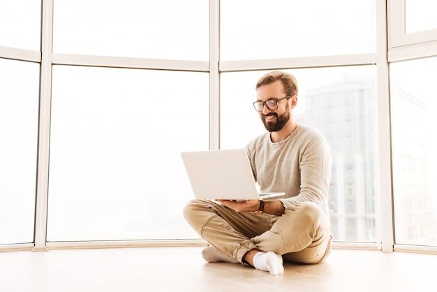 ラップトップコンピューターで作業して笑みを浮かべて男の肖像