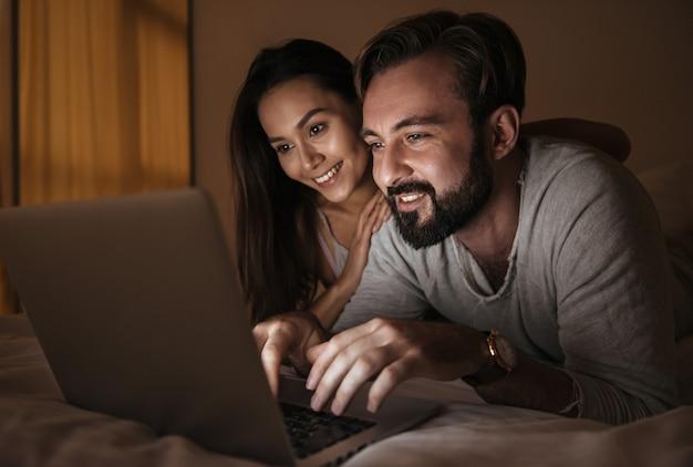 ラップトップを使用して幸せな若いカップルの肖像画