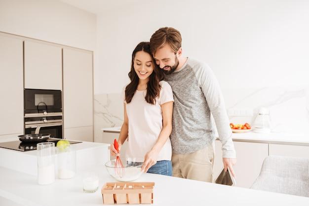 Счастливая молодая пара взбивает тесто для теста