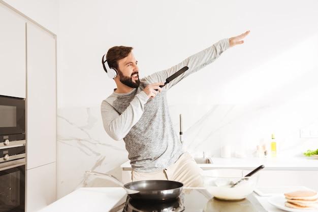 パンケーキを調理する陽気な若い男の肖像