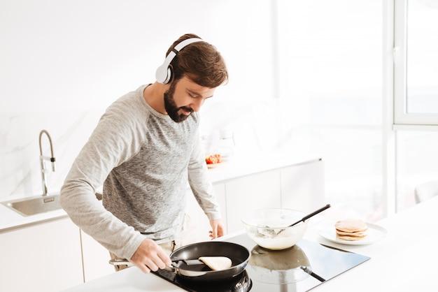 パンケーキを調理する集中して若い男の肖像