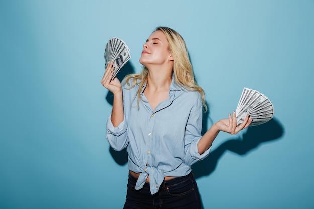 Довольно молодая удивительная блондинка женщина держит в руках деньги.
