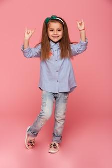 Изображение в полный рост забавной маленькой девочки, жестикулирующей знак скалы двумя руками
