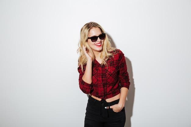 Солнечные очки жизнерадостной молодой белокурой женщины нося