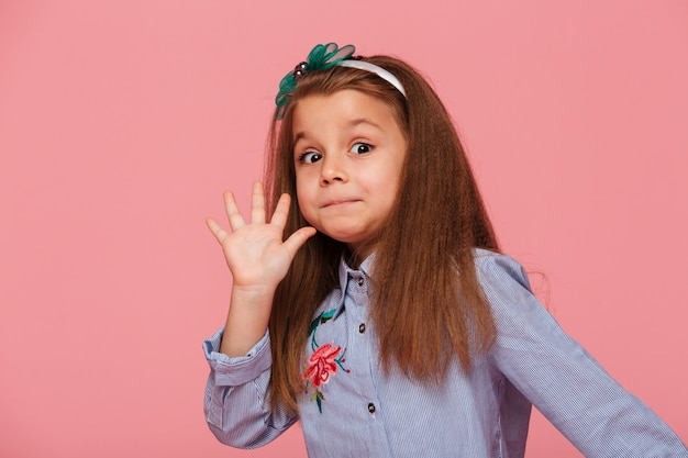Портрет смешного женского ребенка, имеющего длинные каштановые волосы, глядя, давая высокие пять означает привет или пока рукой
