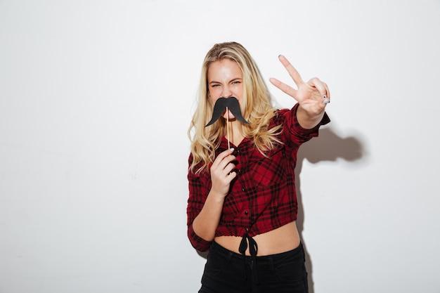 平和のジェスチャーを示す偽の口ひげを保持している若い女性。