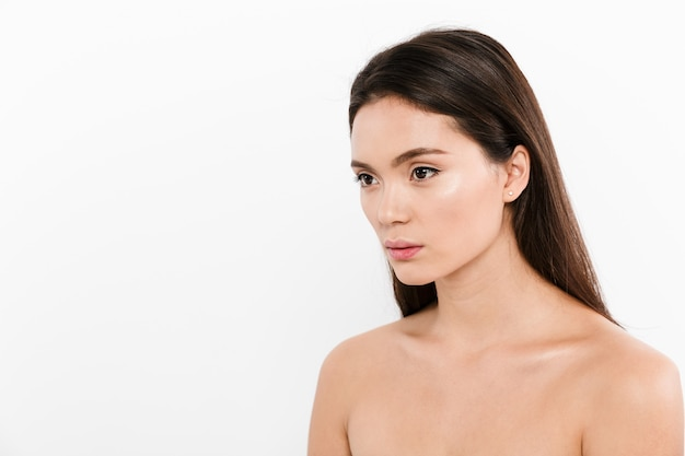 Портрет красоты в пол оборота азиатской милой женщины с коричневыми длинными волосами, изолированной над белизной