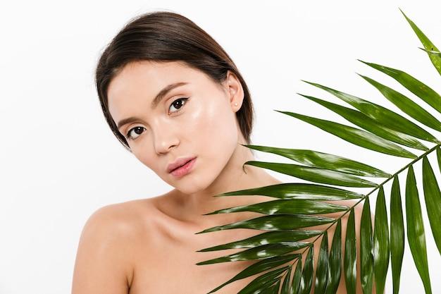 Портрет красотки шикарной азиатской женщины с коричневыми волосами представляя с зелеными листьями, изолированный над белизной