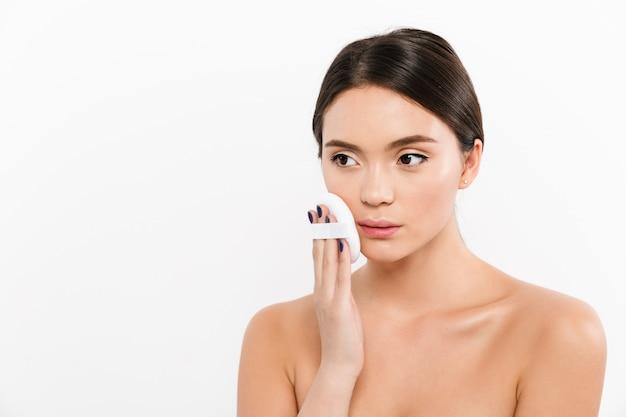 Изображение милой женщины с чистой здоровой кожей, применяя тональный крем или пудру на лице с косметической губкой, изолированных на белый