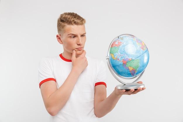 Портрет задумчивого подростка, глядя на глобус