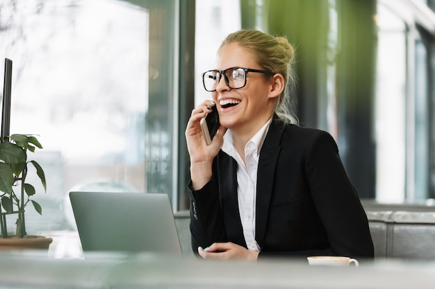 Улыбающаяся блондинка деловая женщина разговаривает по мобильному телефону