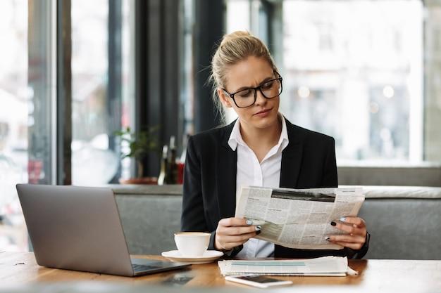 ビジネスの女性が新聞を読んで集中しています。