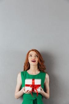 驚きのギフトボックスを保持している驚きの赤毛の若い女性。