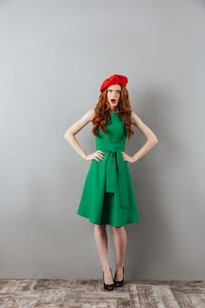 Рыжая молодая кричащая леди в зеленом платье и красном берете