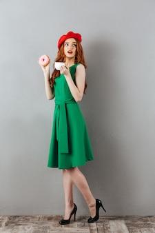 Рыжая молодая милая леди ест пончик и пить кофе.