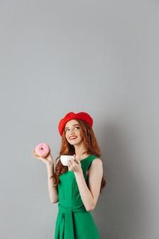 フレンチスタイルのコーヒーのカップを手で押し、灰色の壁に分離されたおいしいドーナツを食べて赤いベレー帽を着ているかわいい生姜女性の肖像画