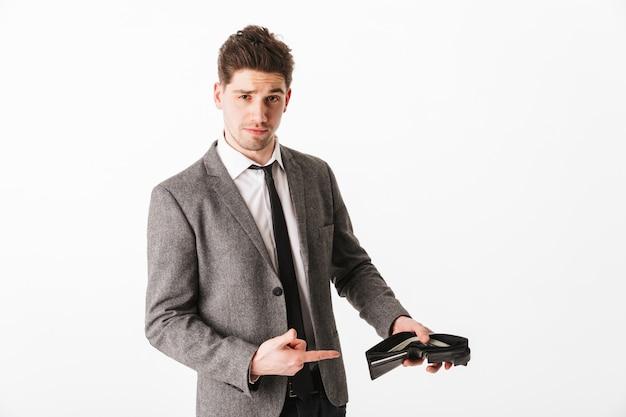 Довольный деловой человек в куртке, показывая свой кошелек с деньгами и указывая на него над белой стеной