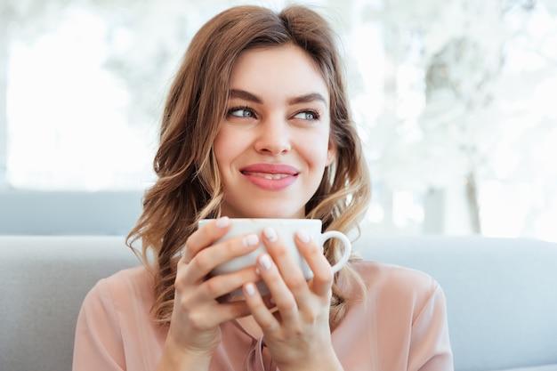 Портрет довольной молодой женщины, держащей чашку кофе