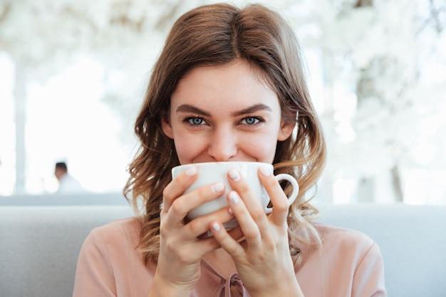 Портрет улыбающейся молодой женщины, держащей чашку кофе