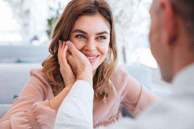 Фотография влюбленной женщины, смотрящей на своего мужчину и получающей удовольствие, держа мужскую руку на ее лице, встречаясь в ресторане