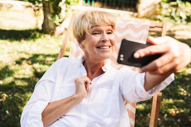 Счастливая зрелая женщина, принимая селфи