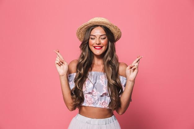 Образ красивой женщины в соломенной шляпе, скрестив пальцы и молиться или мечтать о удаче