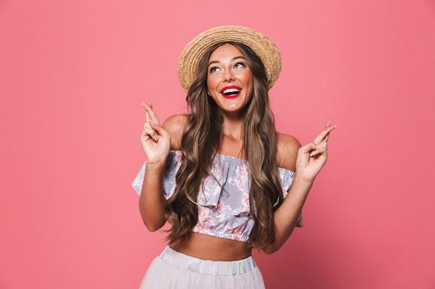 Образ очаровательной молодой леди в соломенной шляпе, скрестив пальцы и молясь или мечтая о удаче