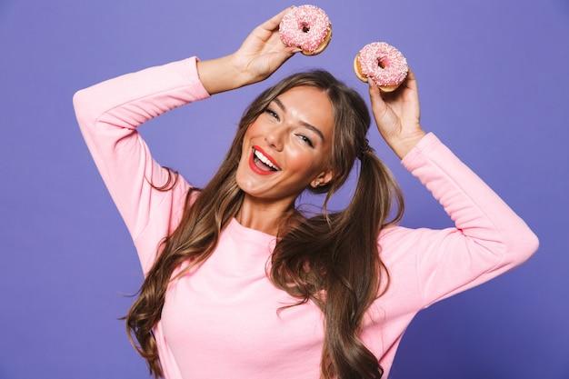 Портрет счастливой женщины в толстовке позирует с пончиками