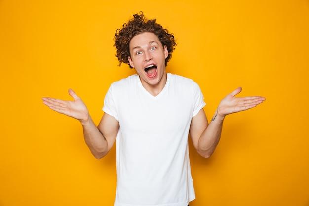 Молодой счастливый человек с каштановыми вьющимися волосами, выкрикивая руки